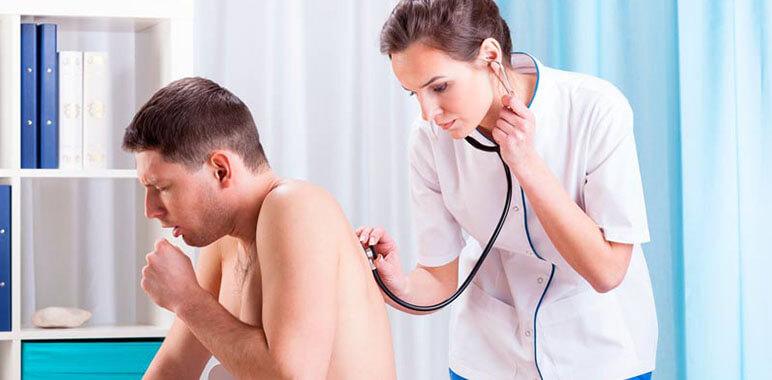 Доктор слушает легкие пациента