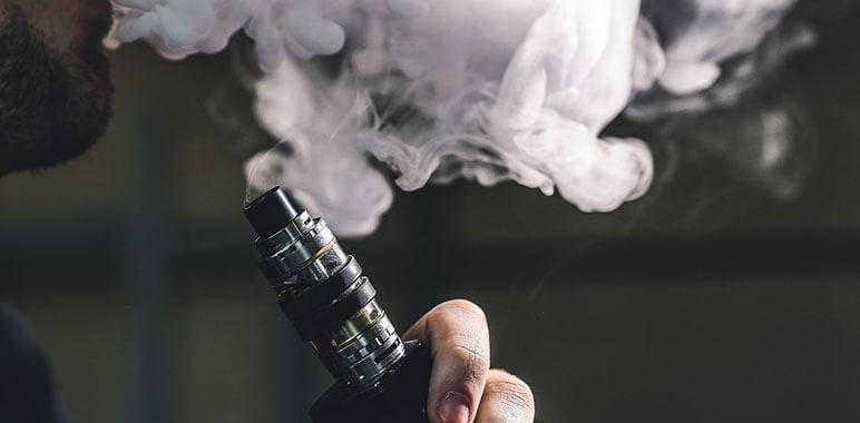 Мужчина курит вейп